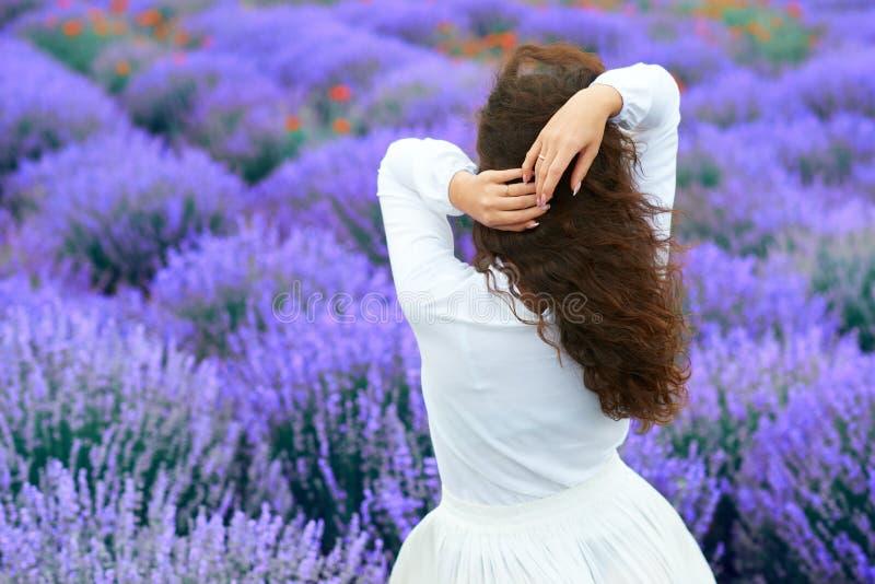 A jovem mulher est? para tr?s no campo de flor da alfazema, paisagem bonita do ver?o imagens de stock