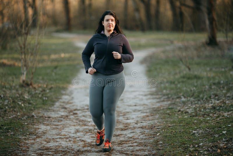 Jovem mulher excesso de peso que movimenta-se no parque fotografia de stock