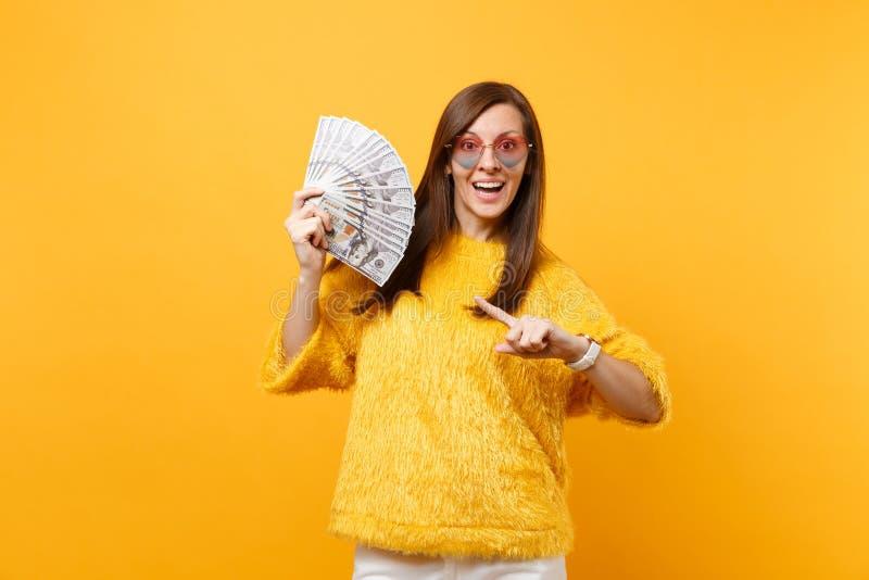 Jovem mulher excitada em monóculos do coração que aponta o indicador em lotes do pacote dos dólares, dinheiro do dinheiro isolado foto de stock