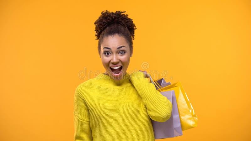 Jovem mulher excitada na camiseta amarela ? moda que guarda sacos de compras, desconto fotos de stock royalty free
