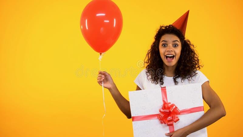 Jovem mulher excitada no chapéu do partido que guarda o balão atual e vermelho, evento do feriado fotos de stock royalty free