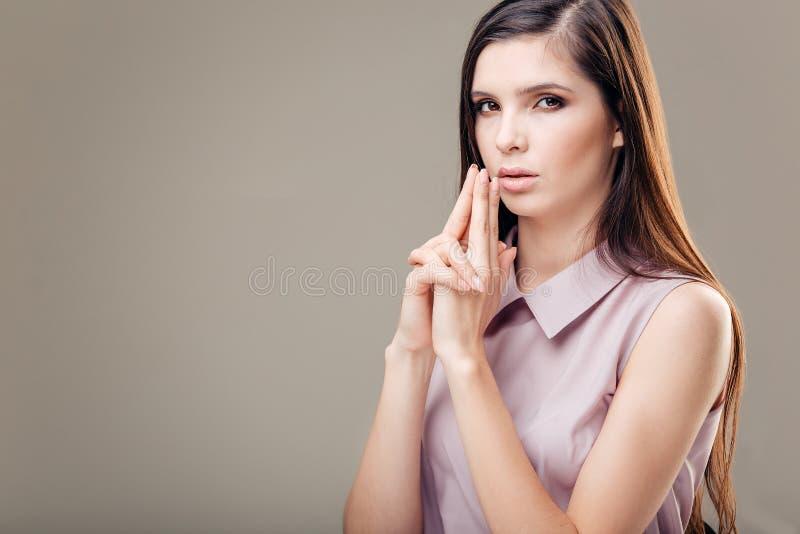 Jovem mulher excitada que faz o sinal da arma da mão com os dedos para o negócio 'sexy' lutar foto de stock