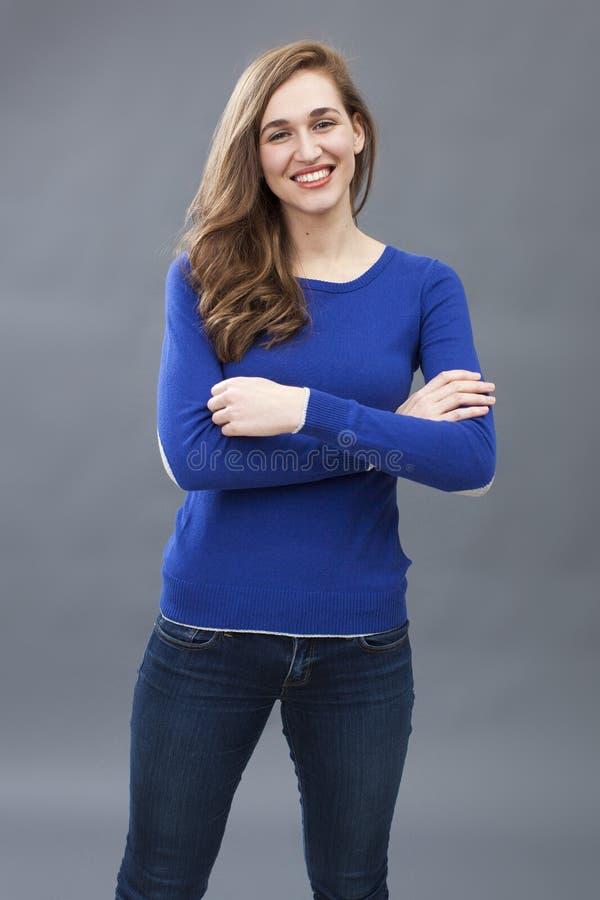 Jovem mulher excitada que levanta com os braços levemente dobrados para o conforto fotografia de stock