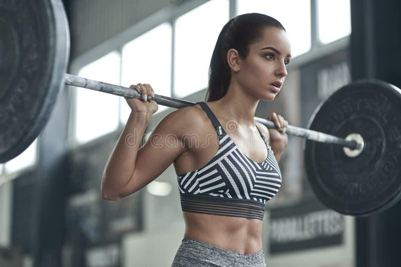 A jovem mulher exercita no estilo de vida saudável do gym pronto para levantar o barbell imagens de stock royalty free