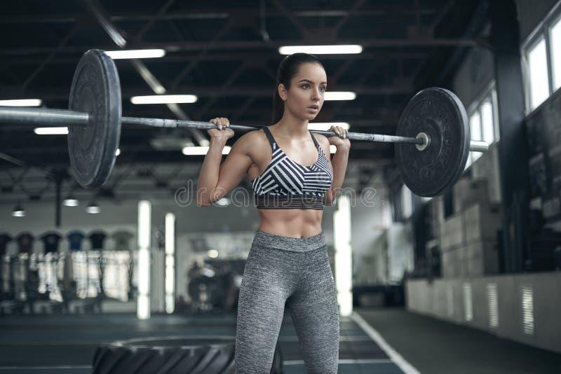 A jovem mulher exercita no estilo de vida saudável do gym pronto para levantar o barbell fotografia de stock royalty free