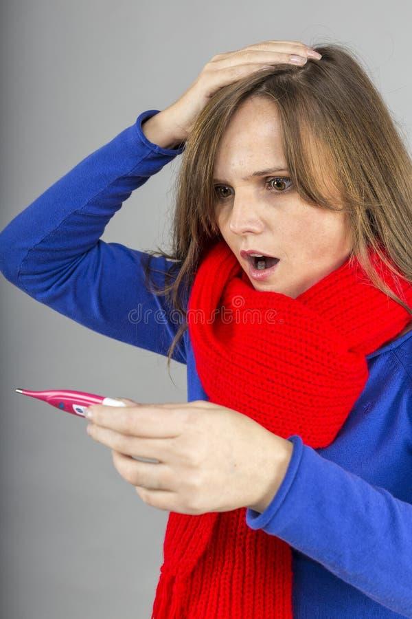 Jovem mulher expressivo que está com a gripe e que verifica o termômetro fotos de stock