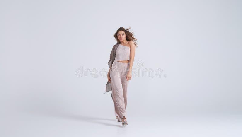 Jovem mulher fabulosa no equipamento à moda que anda para a câmera imagens de stock