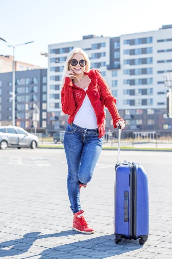 A jovem mulher fala no móbil suitcase O conceito do trave imagens de stock royalty free