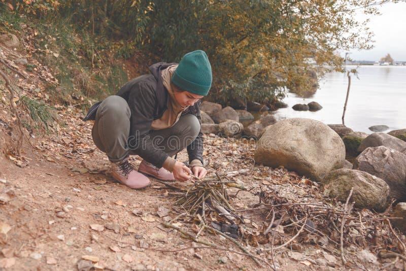 A jovem mulher faz a chaminé na praia foto de stock
