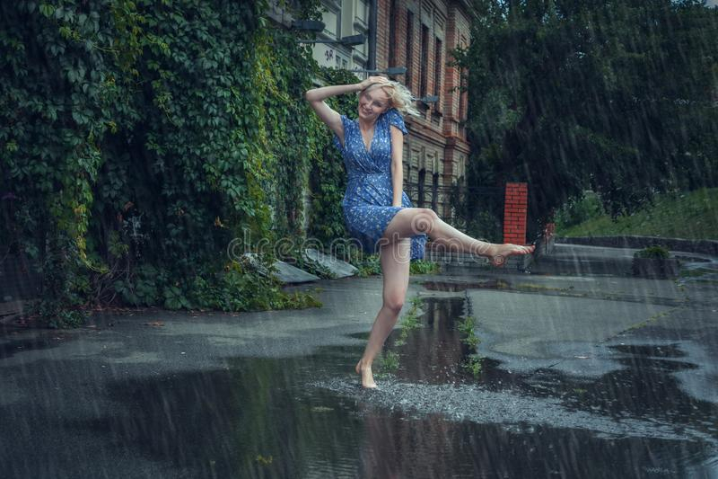 A jovem mulher faz correria na chuva do verão fotografia de stock