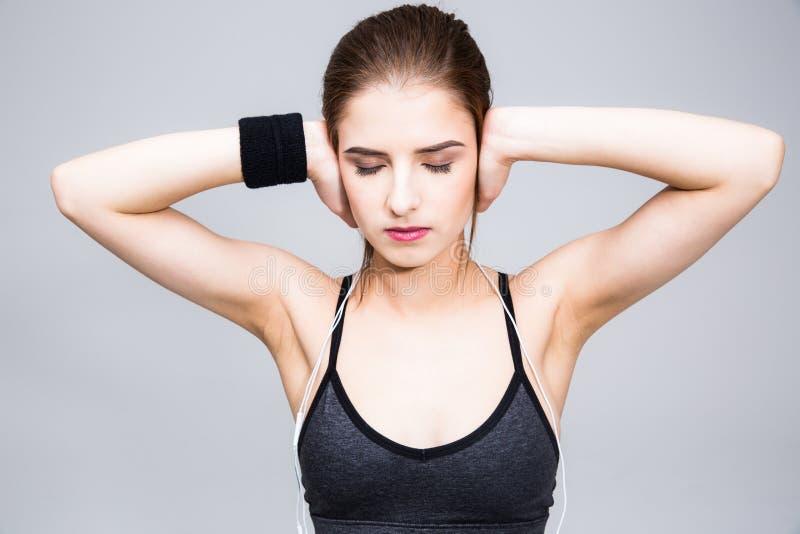 A jovem mulher fecha suas orelhas com seus dedos imagens de stock royalty free