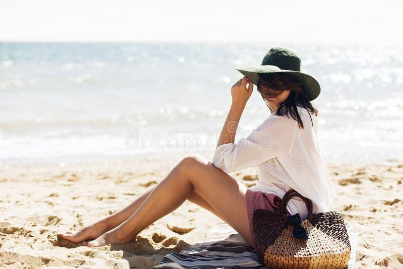 Jovem mulher feliz à moda que relaxa na praia Menina do moderno na camisa branca e no chapéu que sentam-se e que bronzeam-se na p fotografia de stock
