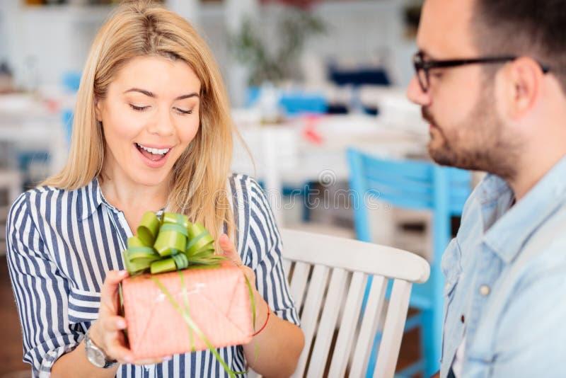 A jovem mulher feliz é surpreendida após ter recebido um presente do aniversário ou do aniversário de seu noivo imagens de stock royalty free