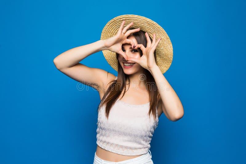 A jovem mulher feliz alegre de sorriso do retrato do close up que faz o sinal do coração com despesas gerais das mãos isolou o fu foto de stock