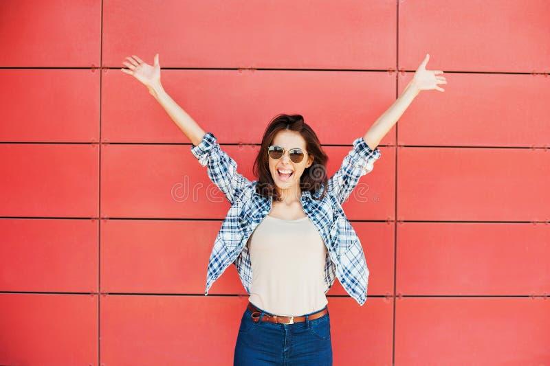 Jovem mulher feliz alegre que salta contra a parede vermelha Retrato bonito entusiasmado da menina imagens de stock royalty free