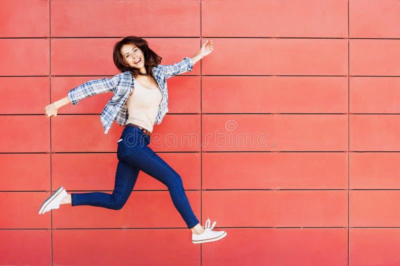 Jovem mulher feliz alegre que salta contra a parede vermelha Retrato bonito entusiasmado da menina fotografia de stock