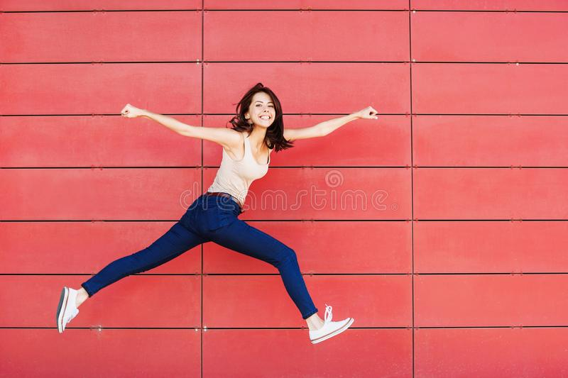 Jovem mulher feliz alegre que salta contra a parede vermelha Retrato bonito entusiasmado da menina fotos de stock royalty free