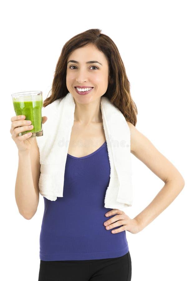 Jovem mulher feliz apta com um vidro do batido verde imagem de stock