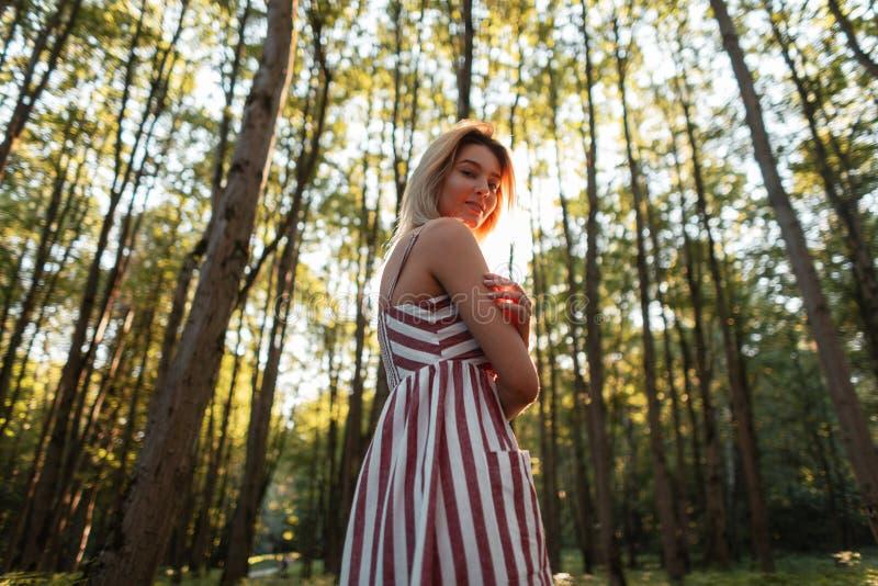 A jovem mulher feliz atrativa no sundress listrados cor-de-rosa à moda com um sorriso doce relaxa fora Menina alegre imagem de stock royalty free