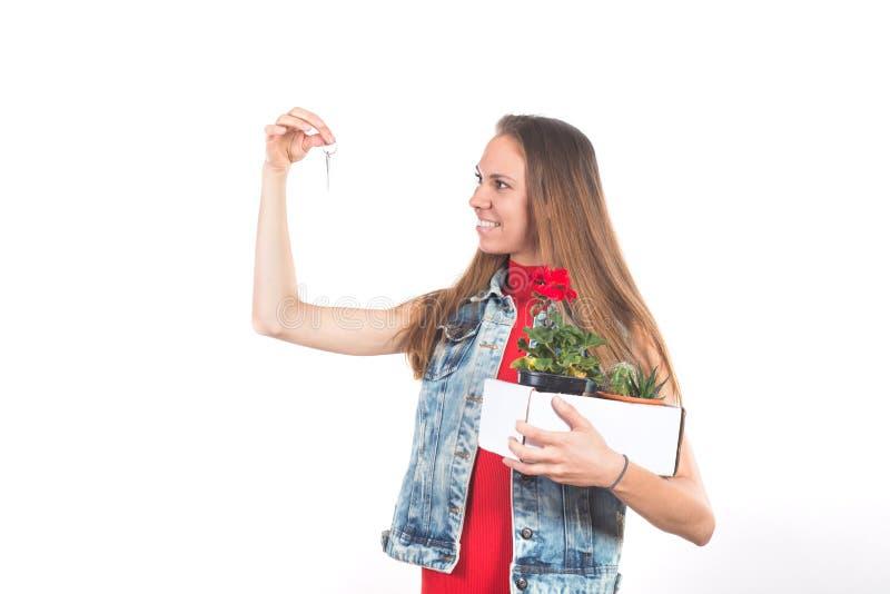 Jovem mulher feliz atrativa que guarda chave da casa nova fotografia de stock royalty free