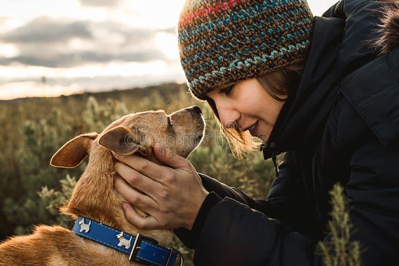 Jovem mulher feliz, beijando e abraçando seu cão Conceito do amor entre a mulher e o cão fotos de stock