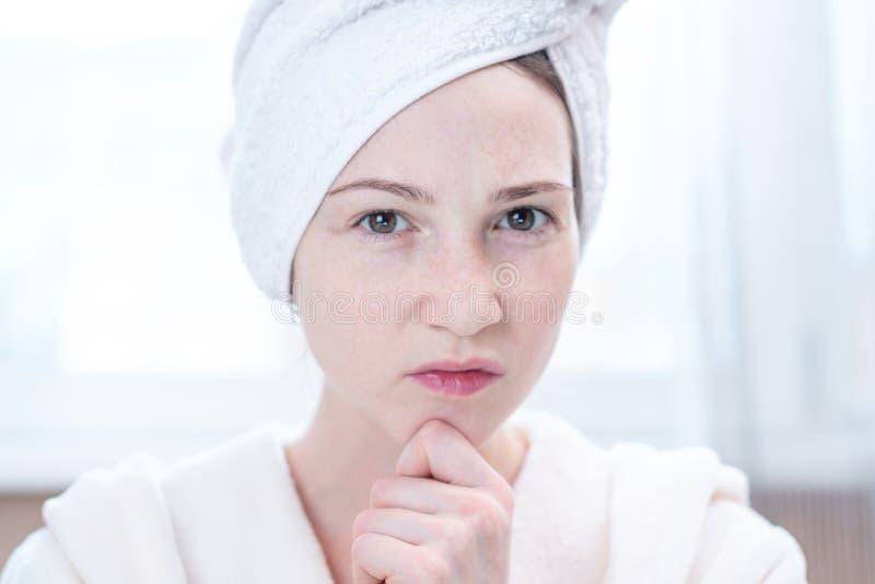 Jovem mulher feliz bonita com uma toalha em sua cabeça que olha sua pele em um espelho Higiene e cuidado para a pele foto de stock
