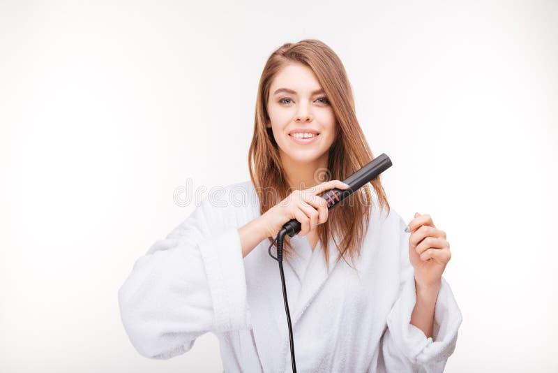 Jovem mulher feliz bonita no roupão usando o straightener do cabelo fotografia de stock