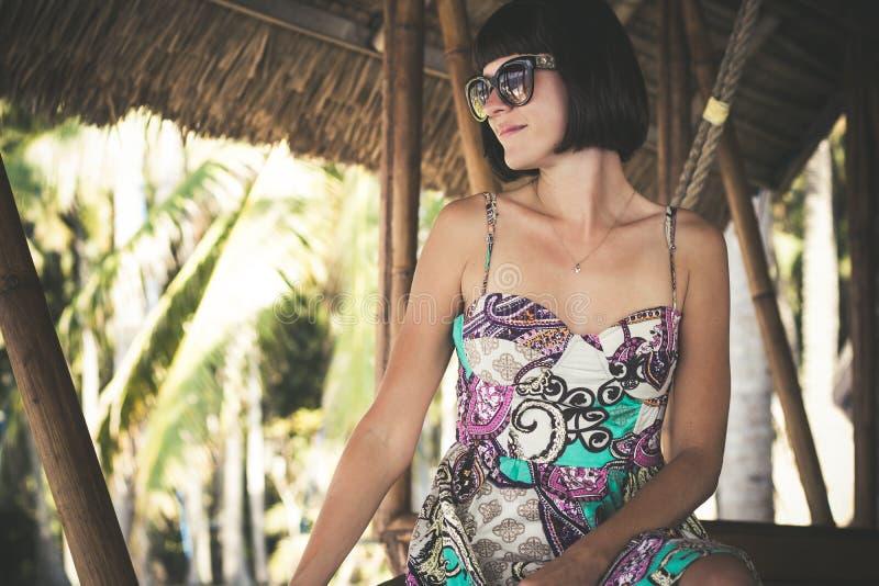 Jovem mulher feliz bonita nos óculos de sol que sentam-se em um miradouro de madeira no dia ensolarado Ilha tropical de Bali, Ind fotografia de stock