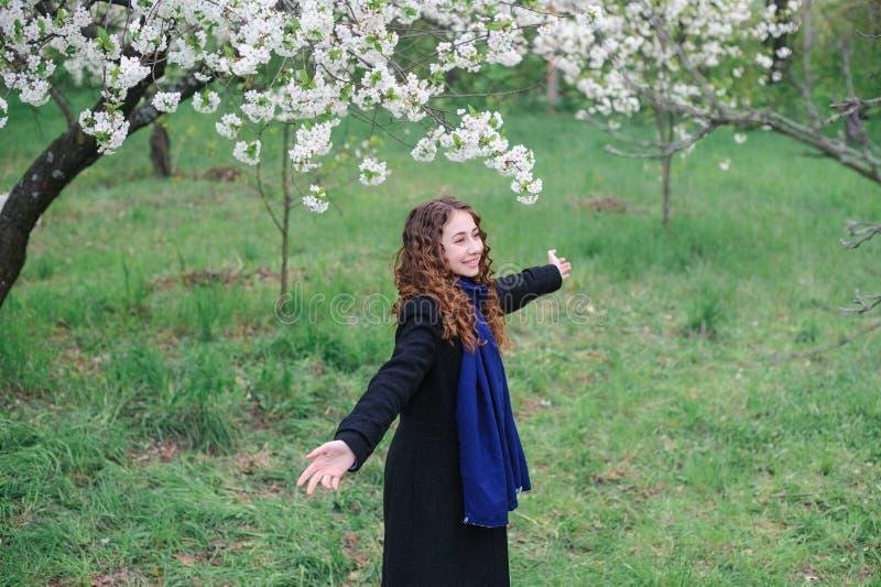 Jovem mulher feliz bonita que anda em um jardim de florescência da mola imagens de stock royalty free