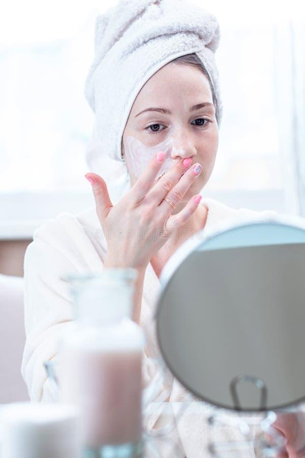 Jovem mulher feliz bonita que aplica o creme na cara que hidrata a pele Conceito da higiene e do cuidado para a pele imagem de stock royalty free