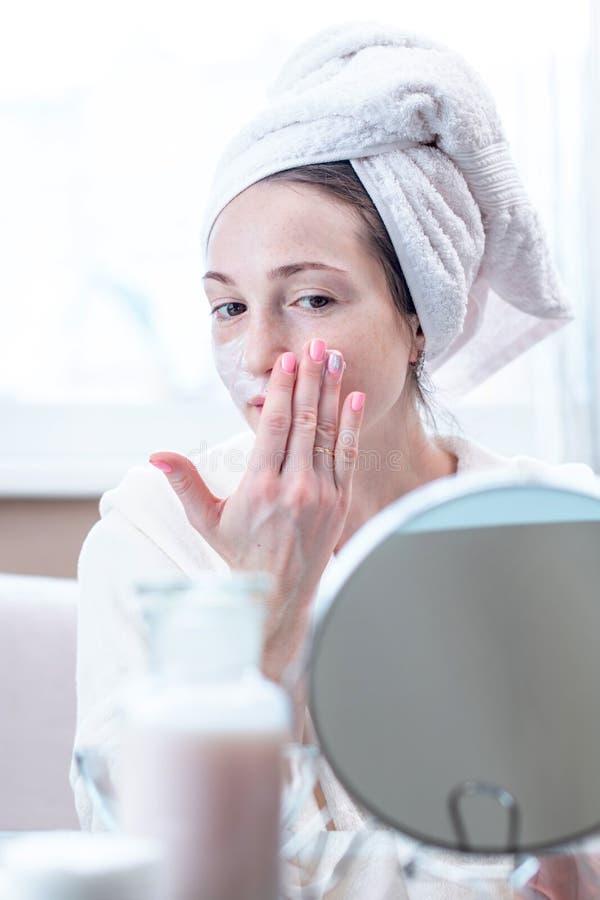 Jovem mulher feliz bonita que aplica o creme na cara que hidrata a pele Conceito da higiene e do cuidado para a pele fotografia de stock royalty free