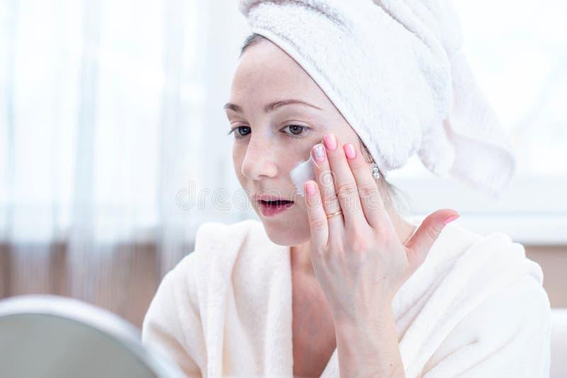 Jovem mulher feliz bonita que aplica o creme na cara que hidrata a pele Higiene e cuidado para a pele em casa imagem de stock royalty free