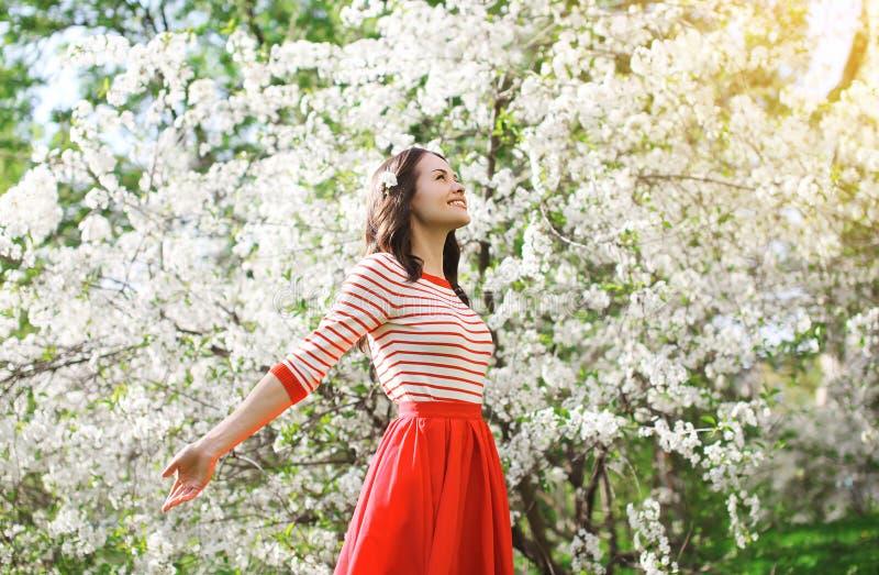 Jovem mulher feliz bonita que aprecia a mola de florescência do cheiro fotos de stock royalty free