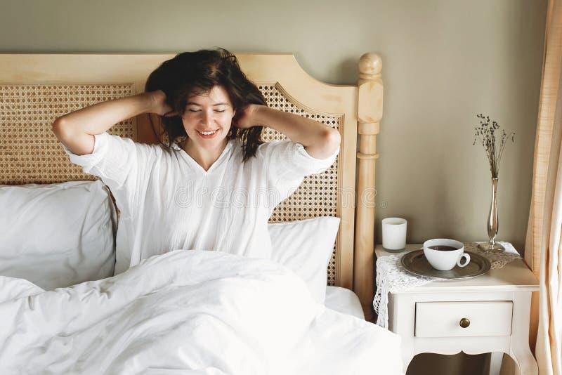 Jovem mulher feliz bonita que encontra-se na cama na manh? na sala de hotel ou no quarto da casa Menina moreno ? moda no relaxame fotografia de stock royalty free