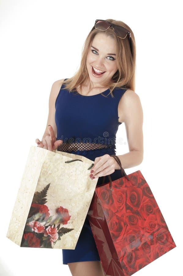 Jovem mulher feliz bonita que guardara sacos do presente da compra. foto de stock