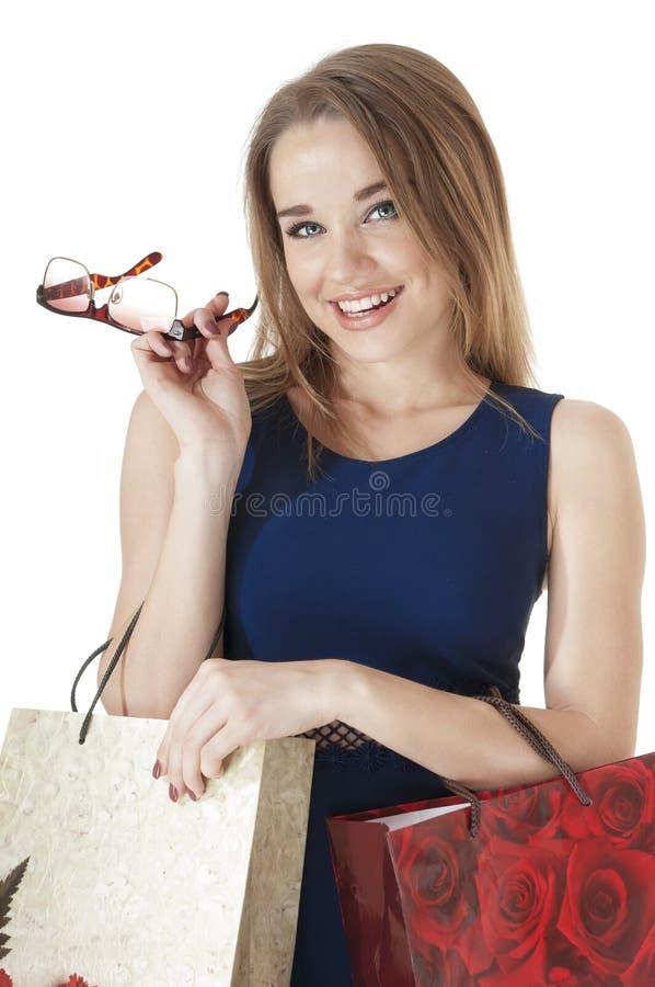 Jovem mulher feliz bonita que guardara sacos do presente da compra. fotografia de stock