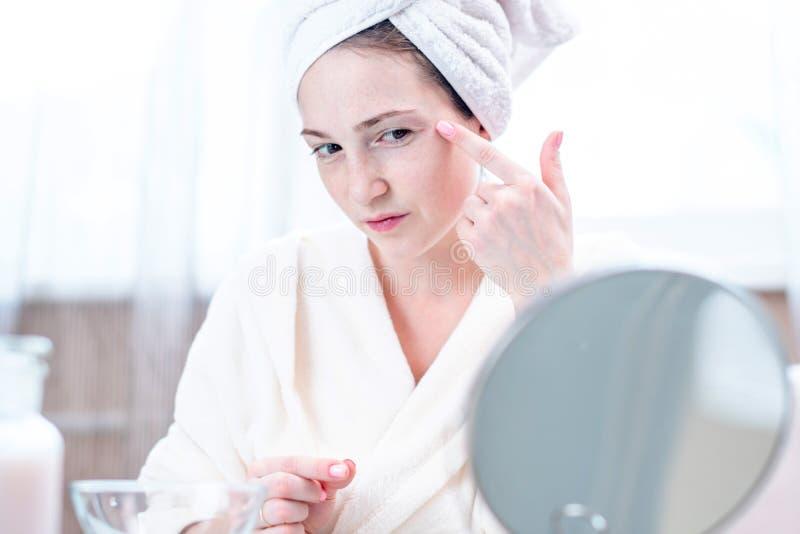 Jovem mulher feliz bonita que olha sua pele em um espelho Conceito da higiene e do cuidado oportunos para a pele imagem de stock royalty free