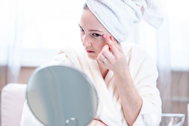 Jovem mulher feliz bonita que olha sua pele em um espelho Conceito da higiene e do cuidado oportunos para a pele fotos de stock