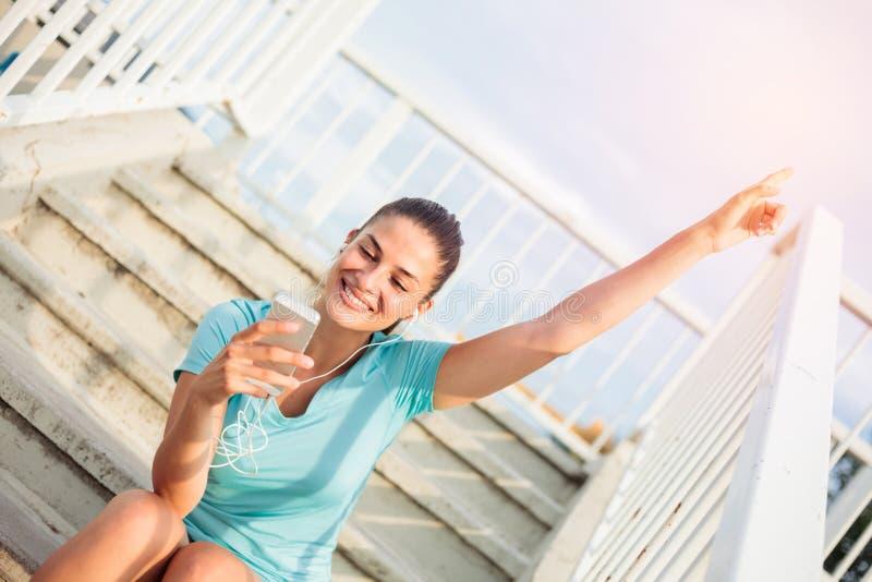Jovem mulher feliz bonita que senta no etapas e que relaxa após um exercício duro imagens de stock royalty free