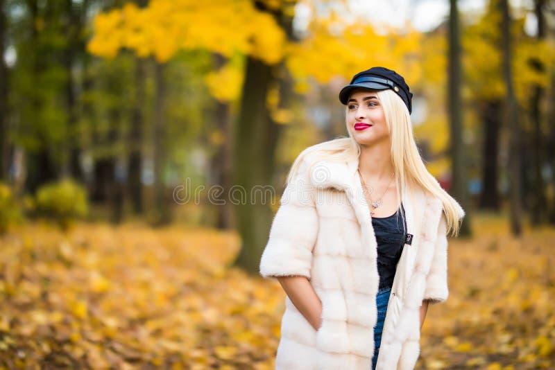 Jovem mulher feliz bonita que tem o divertimento com as folhas no parque do outono fotos de stock