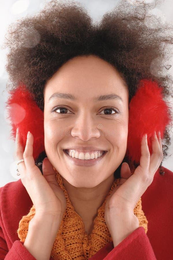 Jovem mulher feliz com as capas protetoras para as orelhas que levantam no estúdio imagens de stock