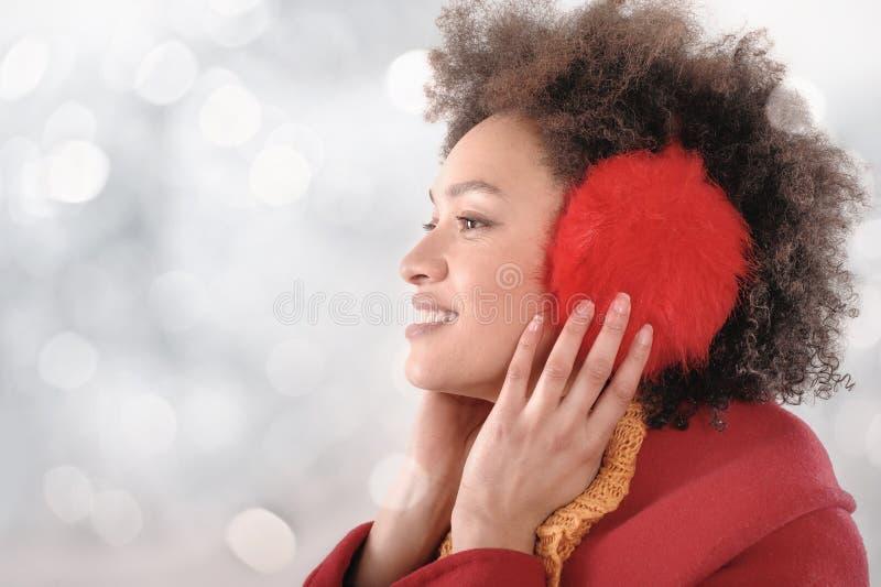 Jovem mulher feliz com as capas protetoras para as orelhas que levantam no estúdio fotografia de stock