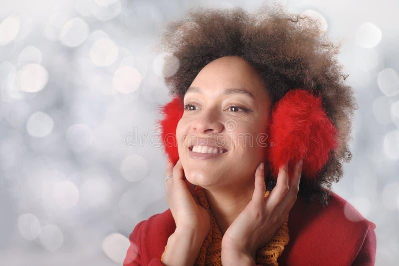 Jovem mulher feliz com as capas protetoras para as orelhas que levantam no estúdio foto de stock