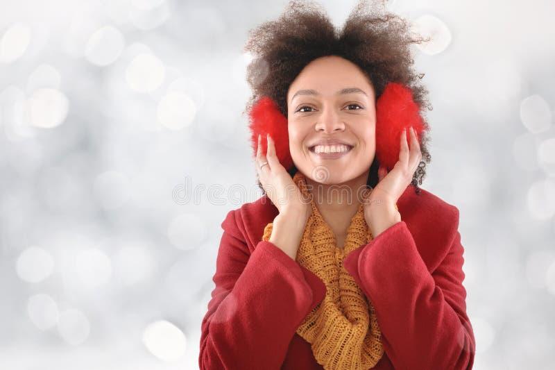 Jovem mulher feliz com as capas protetoras para as orelhas que levantam no estúdio imagem de stock royalty free