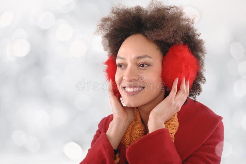 Jovem mulher feliz com as capas protetoras para as orelhas que levantam no estúdio fotos de stock royalty free
