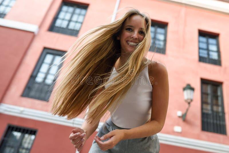 Jovem mulher feliz com cabelo movente no fundo urbano imagem de stock royalty free