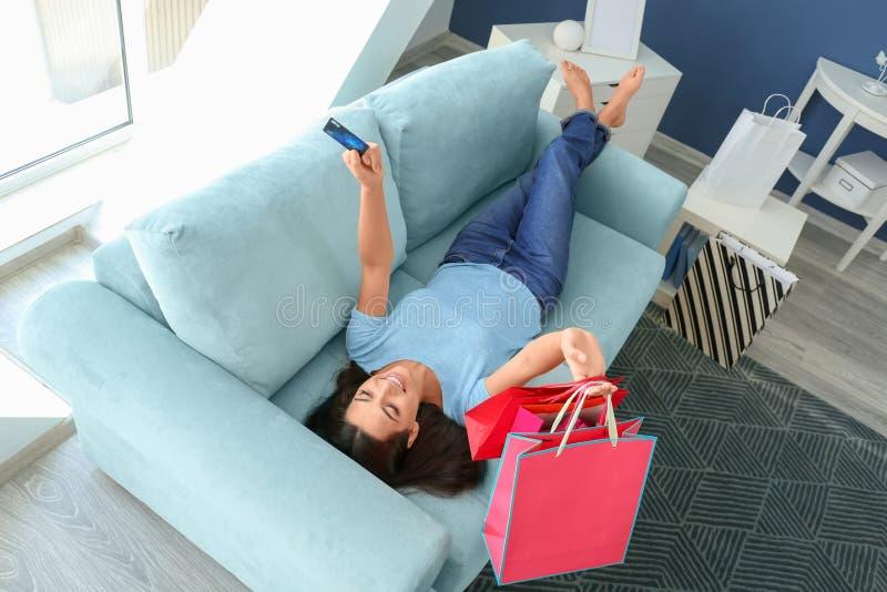 Jovem mulher feliz com cartão de crédito e sacos de compras que encontram-se no sofá em casa imagem de stock