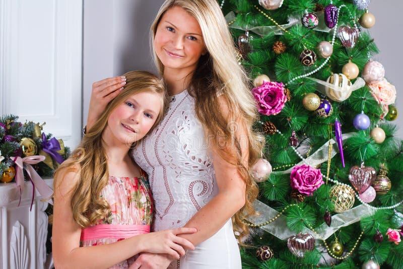 Jovem mulher feliz com a filha adolescente bonito perto do tre do Natal imagens de stock