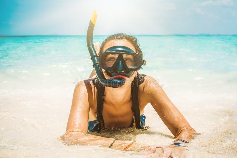 Jovem mulher feliz com mergulhar a máscara que aprecia na praia foto de stock