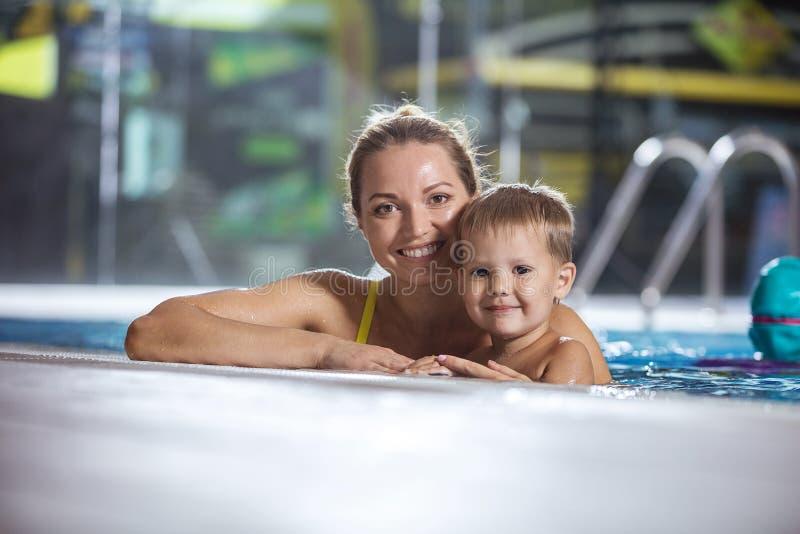 Jovem mulher feliz com o filho pequeno que sorri na piscina interior imagens de stock royalty free